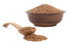 Buckwheat in bowl with wooden spoon on white. Royalty Free Stock Photography