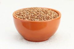 Buckwheat in brown ceramic bowl taken closeup. Stock Photos