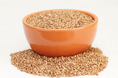 Buckwheat in brown ceramic bowl on a white fabric. Royalty Free Stock Photo