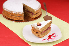 Buckwheat cake. Piece of buckwheat cake with cranberry marmelade decorated with icing sugar and an almond served on a squared white plate. The cake is out of Stock Image