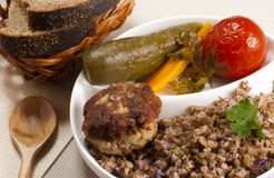 Buckwheat cereal with a cutlet. And pickles stock images