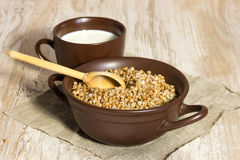 Buckwheat cereal, milk and wooden spoon Stock Images