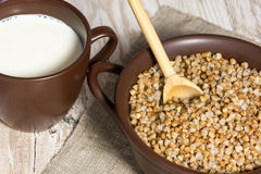 Buckwheat cereal, milk and wooden spoon Royalty Free Stock Photo