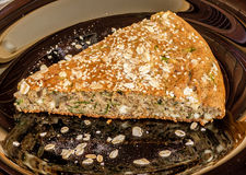 Buckwheat flour and spinach pie with sesame and flakes on black plate Royalty Free Stock Images