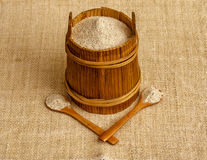 Buckwheat flour in wooden canister with two wooden spoons on sackcloth Stock Images