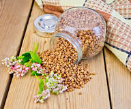 Buckwheat in glass jar on board with flower Royalty Free Stock Images