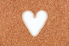 Buckwheat grains and a rope in the shape of a heart with a place for designers. Royalty Free Stock Image
