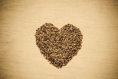 Buckwheat groats heart shaped on wooden surface. Royalty Free Stock Photo
