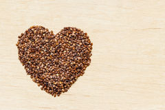 Buckwheat groats heart shaped on wooden surface. Royalty Free Stock Photos