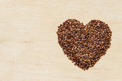 Buckwheat groats heart shaped on wooden surface. Stock Photos