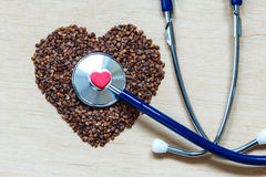 Buckwheat groats heart shaped on wooden surface. Stock Photo