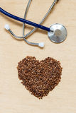 Buckwheat groats heart shaped on wooden surface. Royalty Free Stock Images