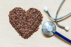 Buckwheat groats heart shaped on wooden surface. Stock Images
