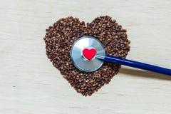 Buckwheat groats heart shaped on wooden surface. Stock Photos