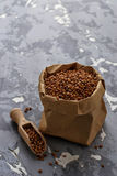 Buckwheat groats in paper bag. Selective focus royalty free stock image