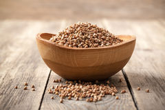 Buckwheat groats in wooden bowl. Close up Stock Photo