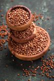 Buckwheat groats in wooden bowl. Selective focus Stock Image