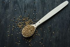 Buckwheat groats in a wooden spoon on a dark wooden background. View from above royalty free stock photos