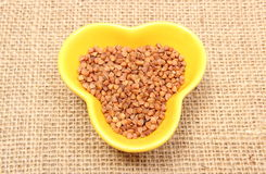 Buckwheat groats in yellow bowl on jute canvas Stock Photography