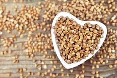 Buckwheat in heart-shaped bowl, gluten free ancient grain for healthy diet stock photography