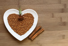 Buckwheat on a heart shaped plate. On wood stock photo