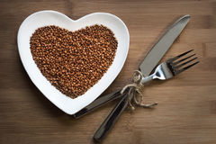 Buckwheat on a heart-shaped plate Stock Image