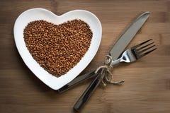Buckwheat on a heart-shaped plate. Buckwheat on a heart shaped plate on wood stock image