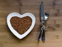 Buckwheat on heart-shaped plate. Buckwheat on a heart shaped plate on wood royalty free stock photos