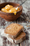 Buckwheat honey in a ceramic bowl and brown bread Stock Photo