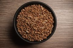 Free Buckwheat In Black Bowl On Wooden Background. Closeup. Royalty Free Stock Images - 50779059