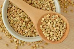 Buckwheat kernels in wooden spoon and bowl. On wooden background Stock Photography