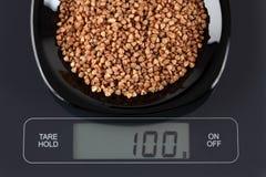 Buckwheat on kitchen scale Stock Photos