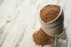 Buckwheat in linen sack into wooden decking. Royalty Free Stock Photos