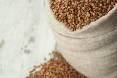 Buckwheat in linen sack into wooden decking. Stock Images