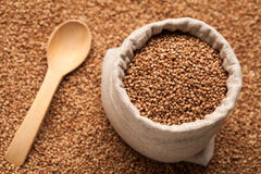 Buckwheat in linen sack with wooden spoon. Royalty Free Stock Photos