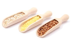 Buckwheat, millet and barley groats with wooden spoon. White background Stock Photography