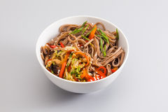 Buckwheat noodles bowl with fried vegetables and shiitake mushrooms. dish on a gray background, close-up Royalty Free Stock Photo