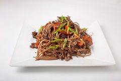 Buckwheat noodles with chicken teriyaki on a white background Stock Photography