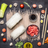 Buckwheat noodles with ingredients, glass noodles with soy sauce and ginger, Asian cuisine on wooden rustic background top view cl royalty free stock image
