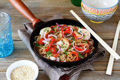 Buckwheat noodles with shrimp, peppers and tomatoes in a frying royalty free stock photo