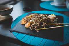 Buckwheat noodles with shrimps and shavings of tuna with sauce on black plate. Asian food background. Eating concept. Restaurant p Royalty Free Stock Photos