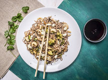 Buckwheat noodles with squid and seafood on a white plate with chopsticks, soy sauce wooden rustic background top view Royalty Free Stock Photography