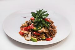 Buckwheat noodles with vegetables and mushrooms in round plate Stock Photo
