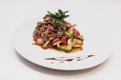 Buckwheat noodles with vegetables and mushrooms in round plate Royalty Free Stock Photo