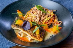 Buckwheat noodles on wok and baked carp. Asian cuisine. The work of a professional chef. Dish from a restaurant or cafe menu. royalty free stock images
