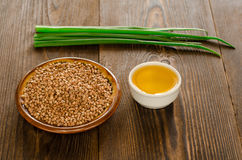Buckwheat with oil and green onions on brown wooden background Stock Photography