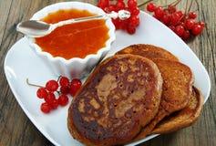 Buckwheat pancakes with apricot jam. Buckwheat pancakes with apricot jam on a wooden table Royalty Free Stock Photos