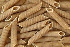 Buckwheat penne pasta. Texture background of raw buckwheat italian pasta Royalty Free Stock Image