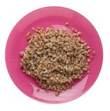 Buckwheat in a plate isolated on white background. buckwheat top view. Healthy food. Buckwheat in a pink  plate isolated on white background. buckwheat top view stock photography
