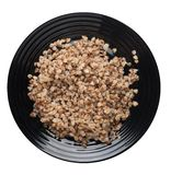 Buckwheat in a plate isolated on white background. buckwheat top view. Healthy food. Buckwheat in a black  plate isolated on white background. buckwheat top view stock photography